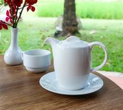 Tea cup and tea pot. On the table royalty free stock photo