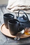 Tea cup with tea pot on a tray. Still life of black tea cup with tea pot on a tray over wooden table. Tea time in a cozy atmosphere stock photography