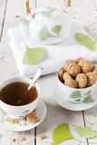 Tea on cup with teapot and amaretti sweets on white table Royalty Free Stock Photos