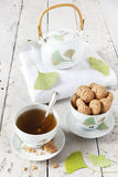 Tea on cup with teapot and amaretti sweets on white table Stock Images