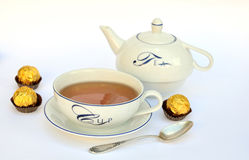 Tea cup, teapot and chocolates Stock Photos