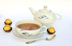 Tea cup, teapot and chocolates Stock Photos