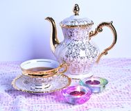 Tea cup and teapot on pink tablecloth Stock Images