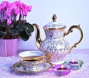 Tea cup and teapot on pink tablecloth Royalty Free Stock Image