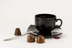 Tea cup, teaspoon & chocolates Royalty Free Stock Photography