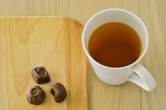 Tea cup and three chocolate candies on a wooden table royalty free stock photo