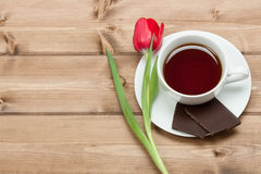 Tea Cup, Tulip Flower, Chocolate. Wooden Table. Top View. Copy S Royalty Free Stock Photos