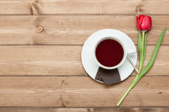Tea Cup, Tulip Flower, Chocolate. Wooden Table. Top View. Copy S Royalty Free Stock Images