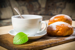 Tea cup with two buns on table Stock Photography