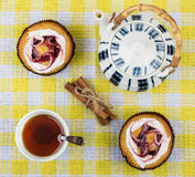 Tea in cup, two cakes, cinnamon sticks and teapot Royalty Free Stock Image