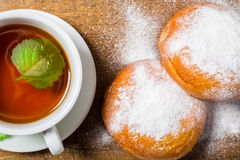 Tea cup with two sugar powdered buns Royalty Free Stock Images