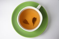 Tea is in a cup, with two tea leaves on Royalty Free Stock Photography