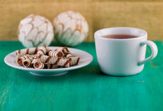 Tea in a cup and wafer tubules in a plate Royalty Free Stock Photos