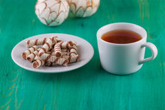 Tea in a cup and wafer tubules in a plate on Royalty Free Stock Images