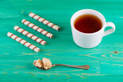Tea in a cup and wafer tubules in a plate Stock Photo
