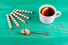 Tea in a cup and wafer tubules in a plate Stock Photos