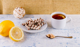 Tea in a cup and wafer tubules in a plate Royalty Free Stock Photography