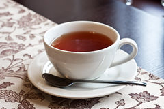 Tea cup whit saucer. The white cup with black tea on dark wood Stock Images