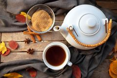 Tea cup and a white teapot on a wooden table with spices and som royalty free stock images