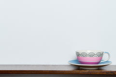 Tea cup on wooden shelf white wall in vintange tone Royalty Free Stock Photo