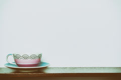 Tea cup on wooden shelf white wall in vintange tone Stock Images