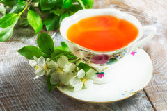 Tea cup on wooden table and apple blossom. Tea cup and apple blossom on wooden table closeup Royalty Free Stock Photography