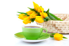 Tea cup with yellow tulips Stock Images