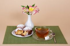 Tea, cupcakes and vase with the flowers Stock Image