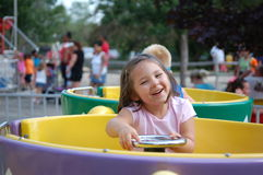 Tea Cups. Four year old girl riding on the tea cups at an amusement park Stock Images