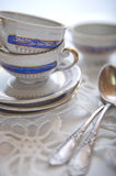 Tea cups. Three tea cups on some plates and silver spoons Royalty Free Stock Images