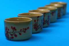 Tea cups. Asian style tea cups in a row  on a blue background Royalty Free Stock Photography