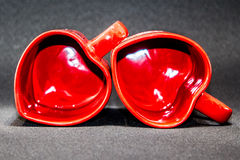 Tea cups love story. Two heart-shaped tea cups on a black background laying on the side Stock Photo