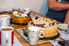 Tea cups mugs with two dessert cake tarts on wooden table at home.  Royalty Free Stock Photography