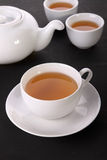Tea cups and pot on table Stock Photo