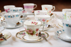 Tea Cups and Silver Spoons. Tea cups decorated with gold rims and flowers Royalty Free Stock Photo