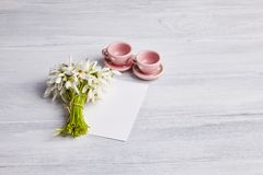 Tea cups and a snowdrops bouquet on the white rusty wooden table royalty free stock photography