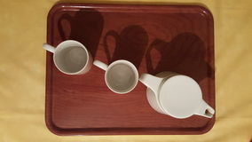 Tea cups and tea pot. Tea cups and pot on wooden tray Stock Image