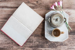 Tea cups with teapot with open book on old wooden table. Royalty Free Stock Images