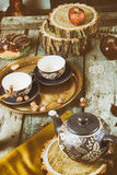Tea cups with teapot on traditional vintage wooden table Stock Images