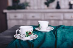 Tea cups on a wooden table with a beautiful velvet tablecloth. Of green color Royalty Free Stock Image