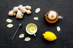 Tea for cure colds. Cup, teapot, ginger root and lemon on black background top view Stock Photos