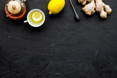 Tea for cure colds. Cup, teapot, ginger root and lemon on black background top view copy space Royalty Free Stock Photos