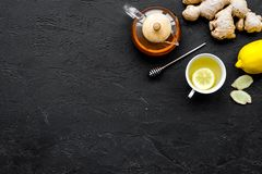 Tea for cure colds. Cup, teapot, ginger root and lemon on black background top view copy space Stock Image