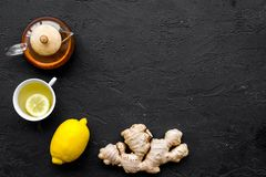 Tea for cure colds. Cup, teapot, ginger root and lemon on black background top view copy space Royalty Free Stock Photography