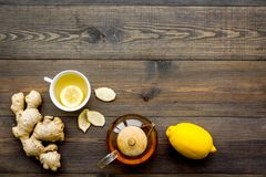 Tea for cure colds. Cup, teapot, ginger root and lemon on dark wooden background top view copy space Royalty Free Stock Image