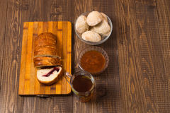 Tea with cutted loaf, jam and buns Stock Images