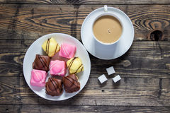 Tea and dainties. Tea in white china mug with three sugar cubes and a plate of iced dainty cakes next to three sugar cubes on a rustic wooden table. Flat-lay stock photos