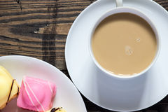 Tea and dainties. Tea in white china mug with three sugar cubes and a plate of iced dainty cakes next to three sugar cubes on a rustic wooden table. Flat-lay stock photography
