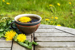 Tea from dandelion in a rustic earthenware cup on a wooden tabl royalty free stock photos