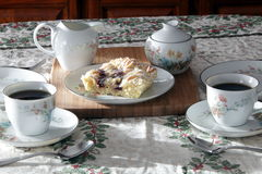 Tea and Danish. Fine floral china service of cups and saucers with a fruit danish pastry Royalty Free Stock Images